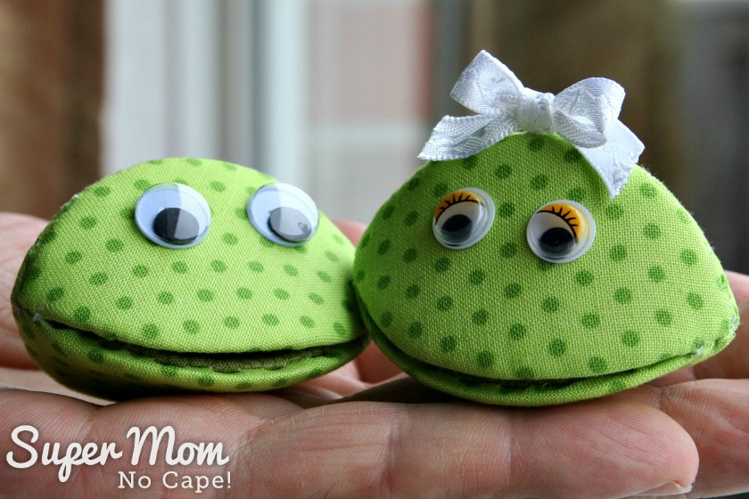 Frankie and Frannie Frog Thimble Pips being held on a man's hand