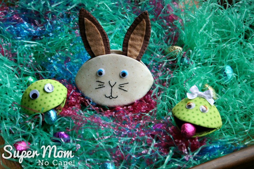 Photo of Frankie and Frannie Frog with chocolate eggs in their mouth and Bennet Bunny sitting between them