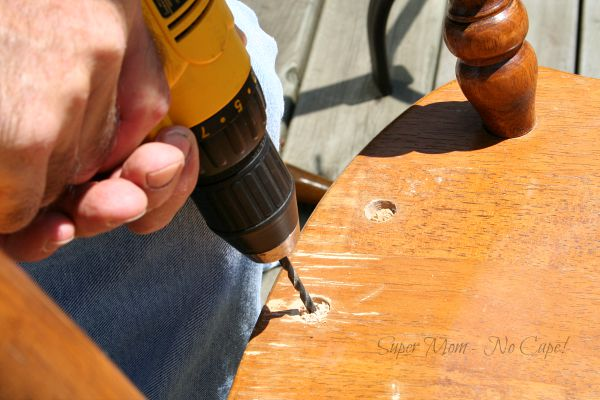 Drill out the broken spindle pieces from the seat of the chair.