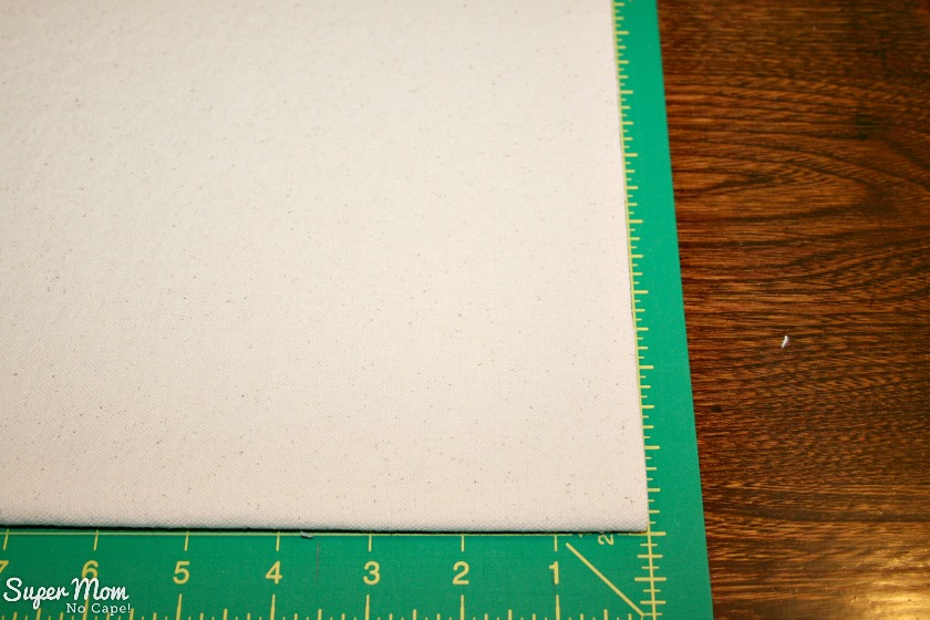 Lining up the edges of the canvas for the Painted Maple Leaf Table Runner with the lines on the cutting mat