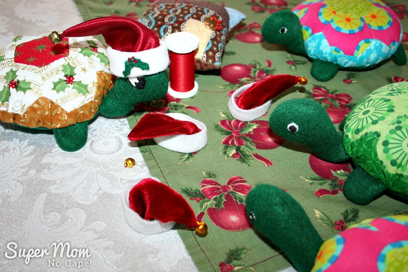 A Hexie Turtle Christmas Eve - Holly Sews bells onto the Hexie Turtles Santa hats