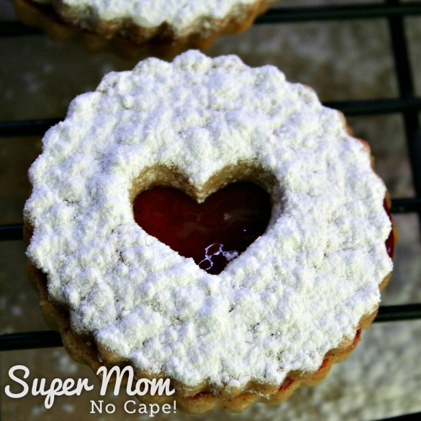 A single Snow Storm Linzer Cookie with the red center looking like stained glass
