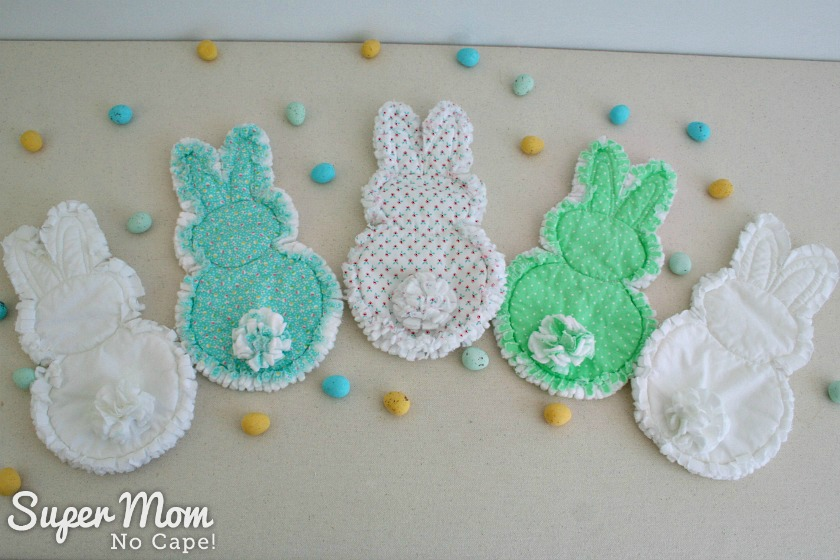 Backs of five rag quilt bunnies with candy eggs