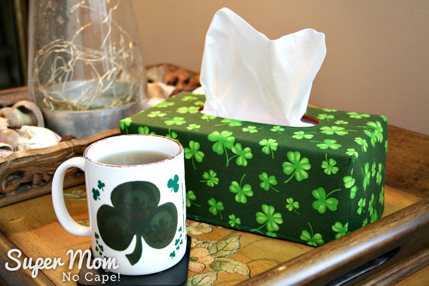 Large shamock fabric tissue box cover on living room side table pictured with a cup of tea