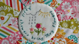 April showers bring May flowers embroidered on a circle with a cloud, rain drops, a sun and flowers in the center