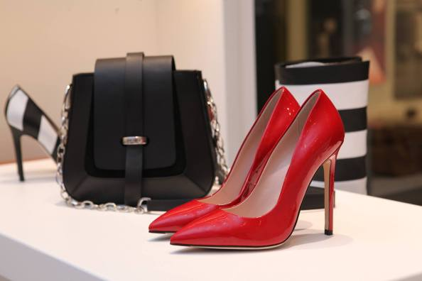 black handbag and red stiletto heals on white countertop