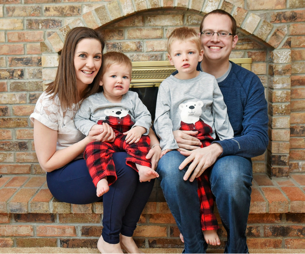family photo, mom with toddler boy and dad with toddler boy sitting in front of fireplace