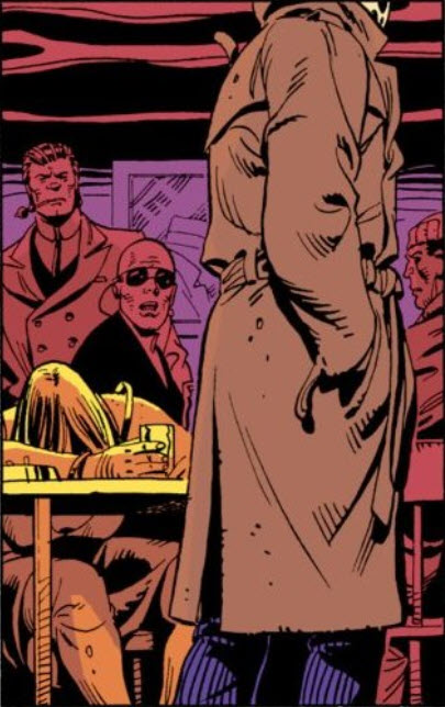 Watchmen chapter 1, page 15, panel 1. A silent panel in which Rorschach walks past a table of people at Happy Harry's, including a bald man in sunglasses, with a cord trailing from them.