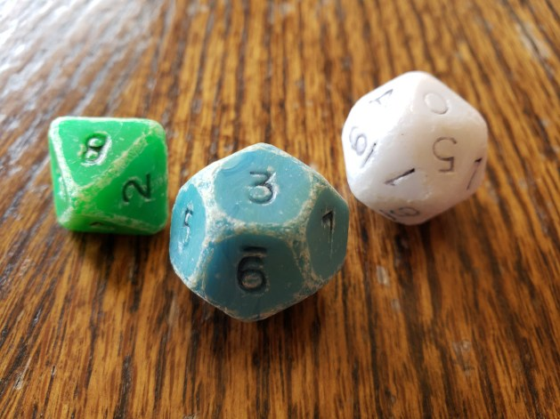 Three very worn plastic dice