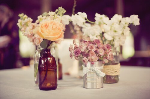 DIY centerpieces using cans and bottles for holding flowers