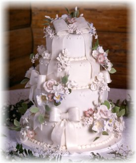 Picture of four tier fondant wedding cake in off white with fondant flowers and bows