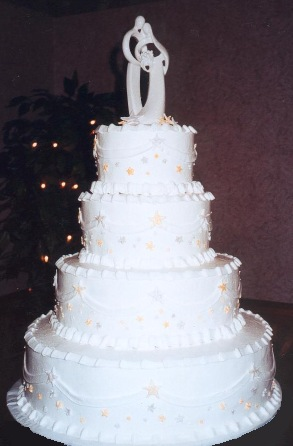 Image of four tier white wedding cake with stars as decorations