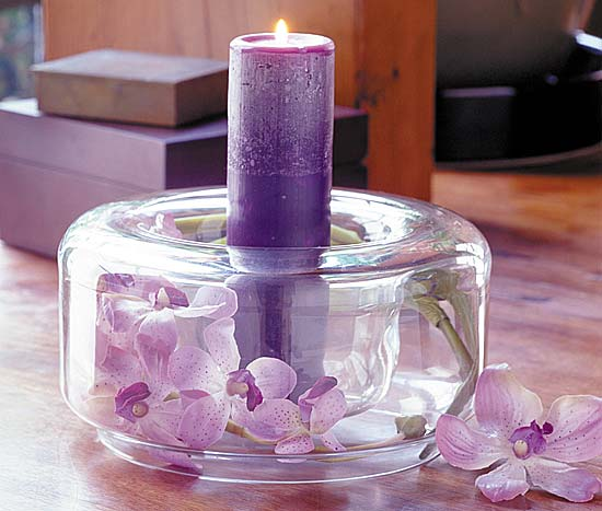 Purple wedding centerpiece with pillar candle and flowers