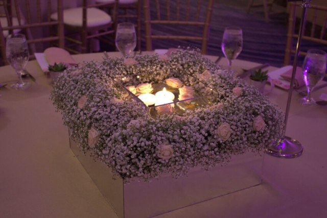 Square floral wreath centerpiece with babys breath and floating candles.