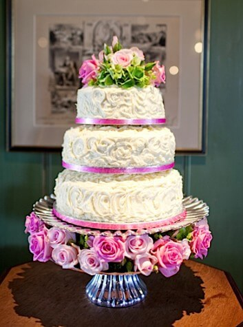 Three Tier White Wedding Cake With Fresh Pink Roses Flowers
