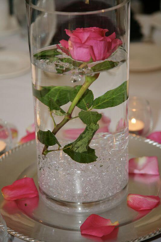 Simple wedding centerpiece idea - single rose on cut stem submerged in water in clear vase