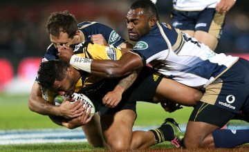 ince Aso of the Hurricanes is tackled by Andrew Smith and Tevita Kuridrani of the Brumbies during the round nine Super Rugby match