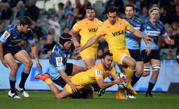 Jaguares' Martin Landajo (C) is tackled by New South Wales Waratahs' Tolu Latu