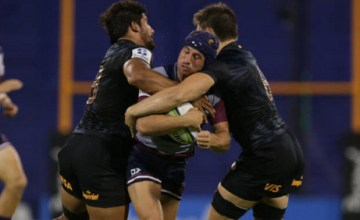 Hamish Stewart of Reds is tackled by Francisco Gorrissen of Jaguares and Tomas Lezana of Jaguares