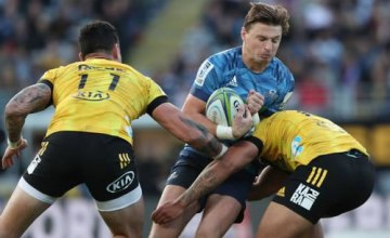 Blues' Beauden Barrett (C) is tackled during the Super Rugby match between the Auckland Blues and Wellington Hurricanes