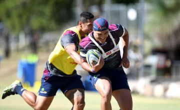 Jordan Petaia attempts to break away from the defence during a Reds Super Rugby training session