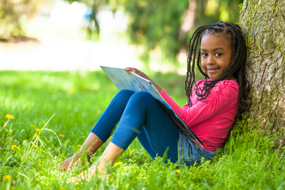 Girl sitting outside against tree, reading