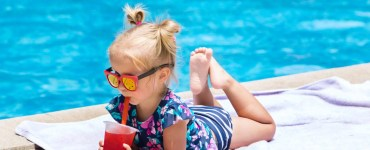 Little girl with cocktail at the swimming pool