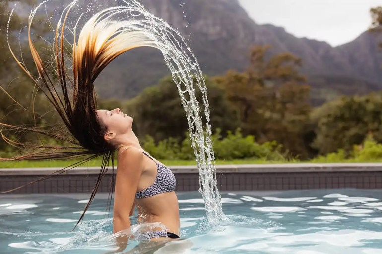 woman flipping her hair in pool