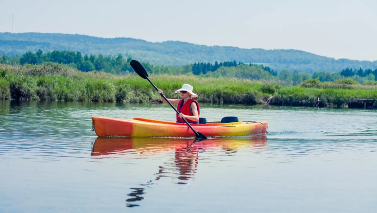 woman with hat kayaking