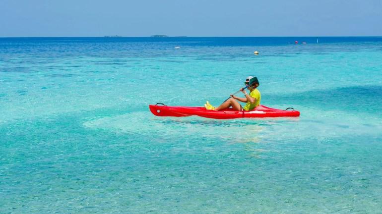 man in paradise water on sit on top kayak