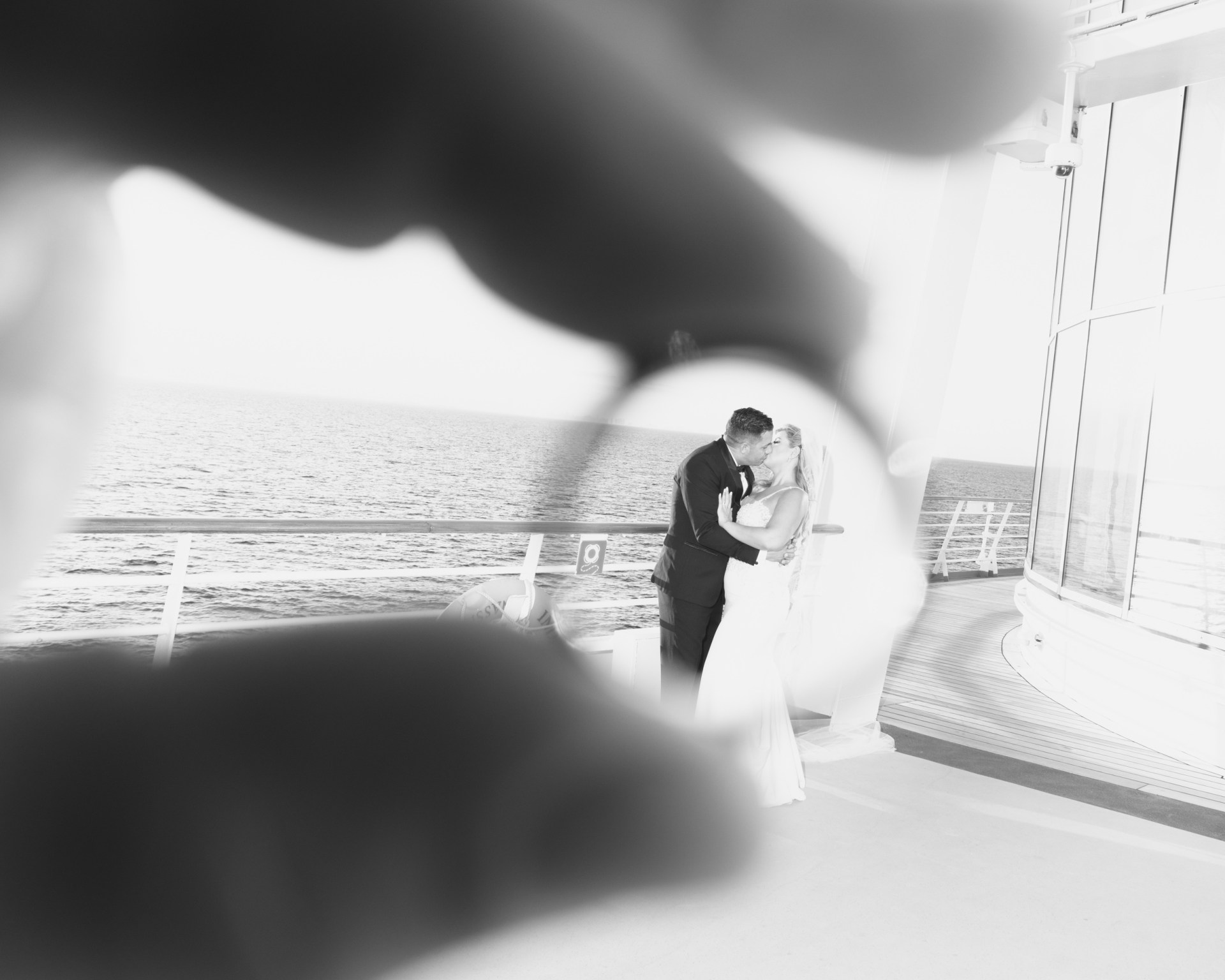 Bride and groom kissing framed by wedding ring