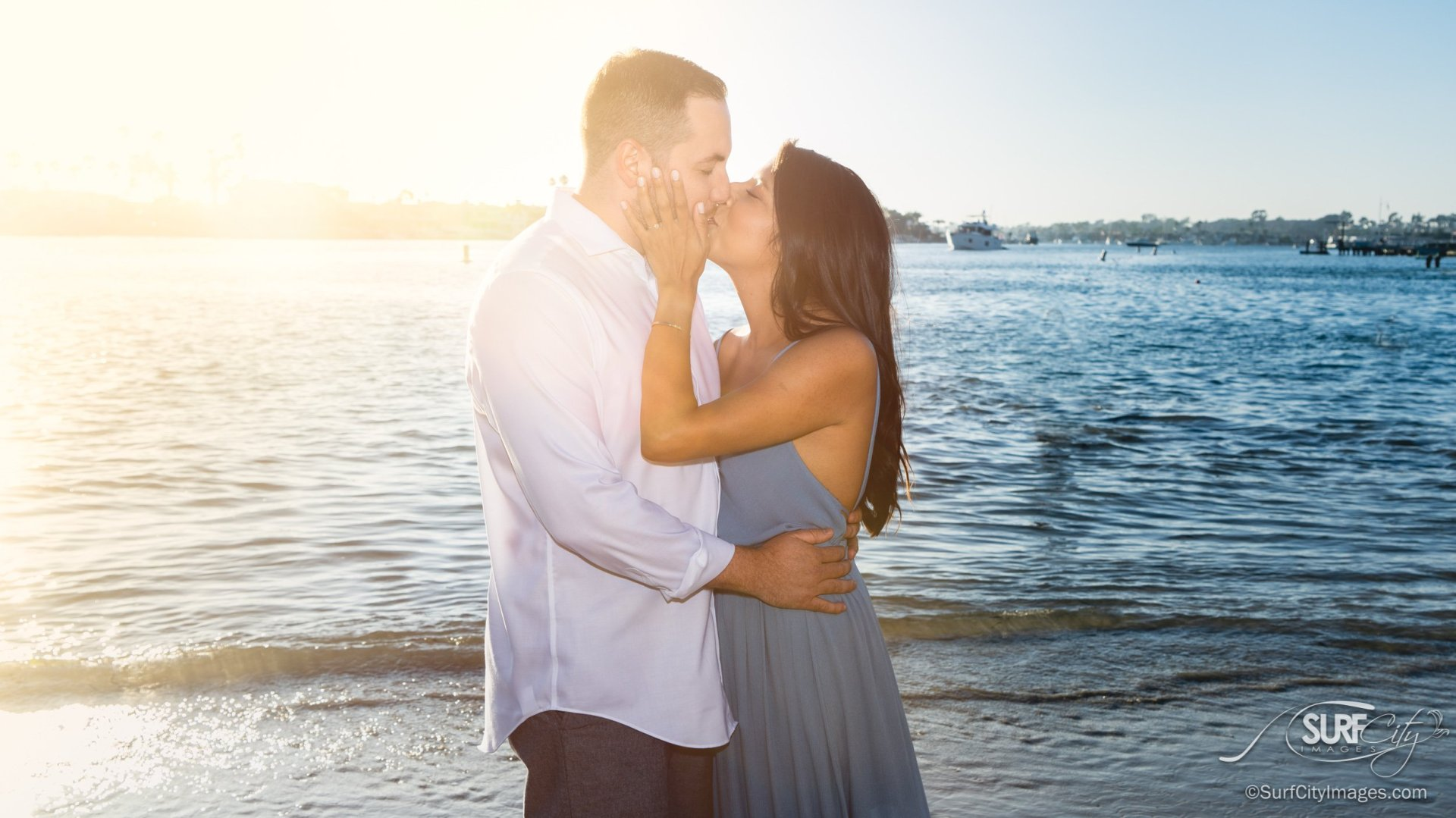 Newly engaged couple kissing at the beach