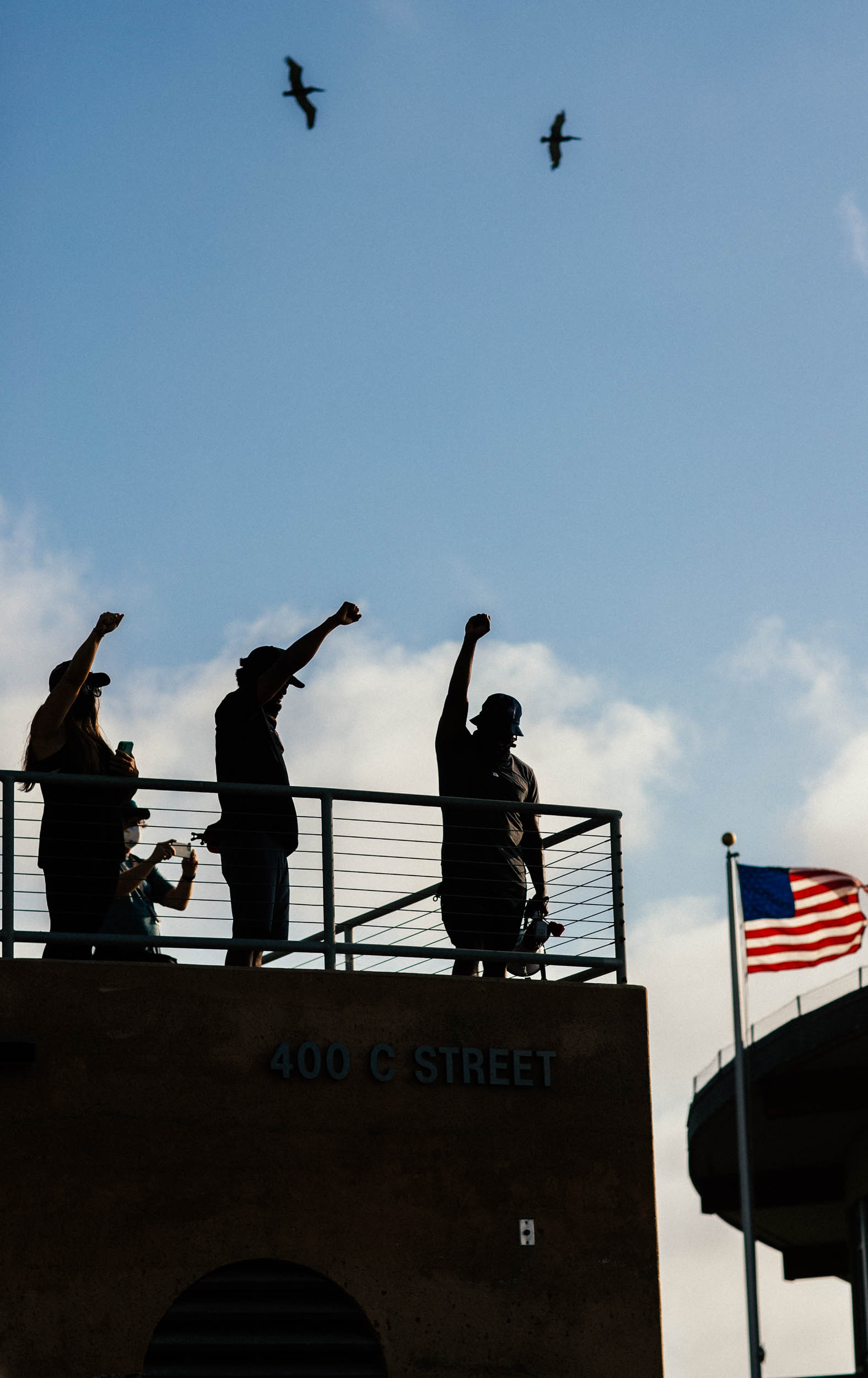 Silhouettes of Sal Masekela, Justin Wilkenfeld (founder of the Kindhumans Movement) and friends raise their fists in a moment of silence.