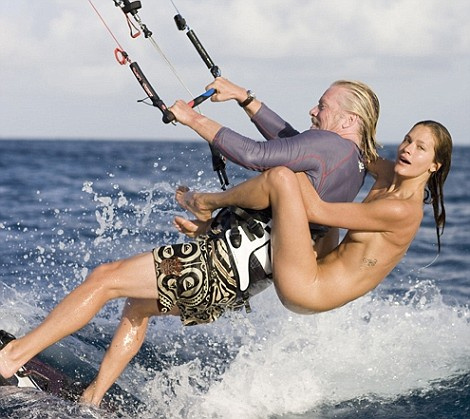 Richard Branson with naked model on his back kiteboarding