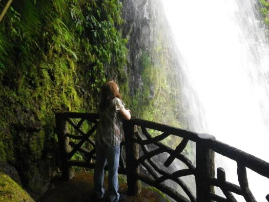 Susan gazing at a waterfall in the jungle