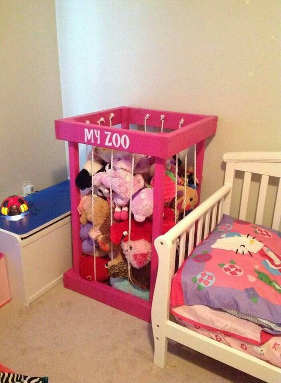 "Pink wooden box with vertical rope ""bars"" used for storing stuffed animals."