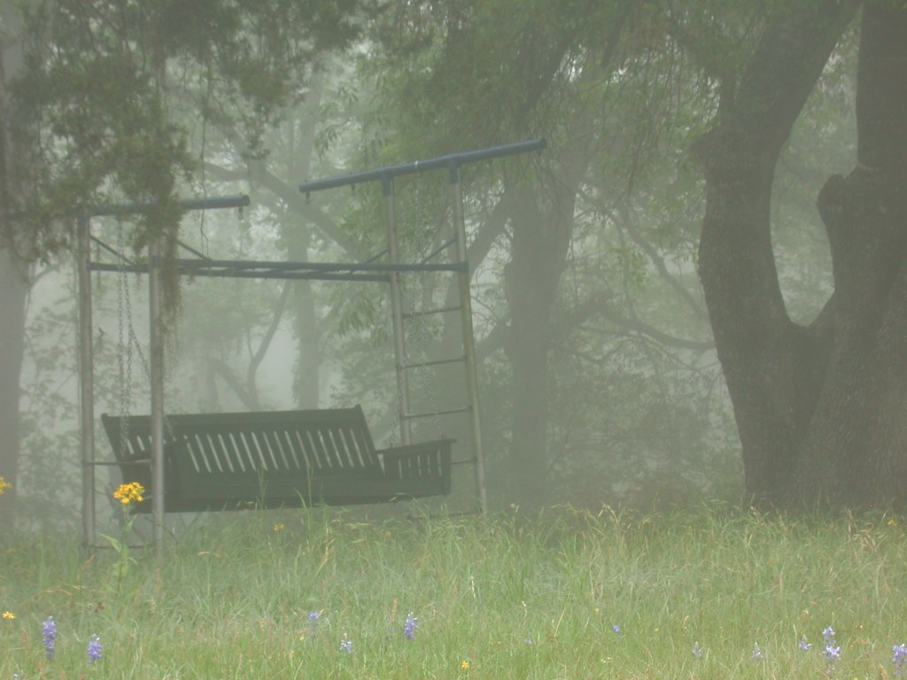 old fashioned porch swing on a misty morning