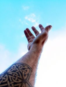 arm with a Celtic tattoo reaching towards the sky from a post at Holy in the Daily