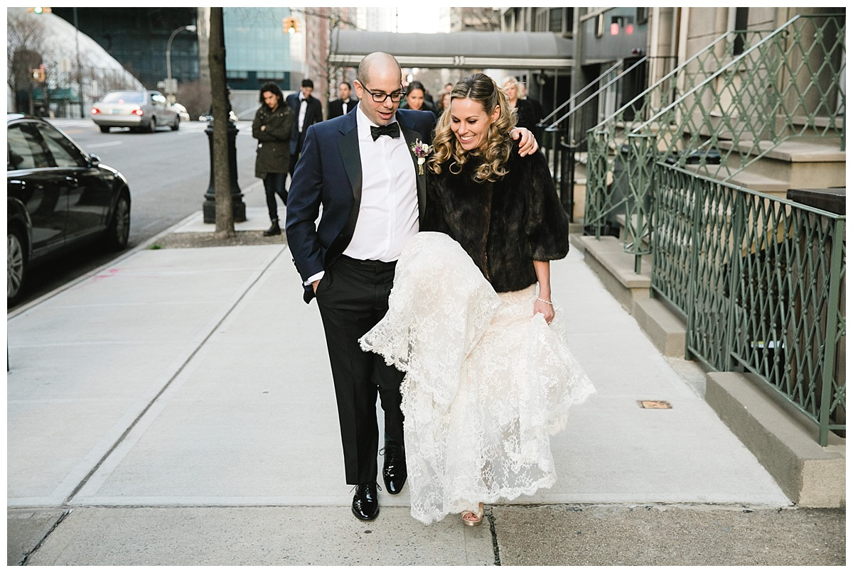 A bride and a groom walking towards their wedding and reception venue on a wedding day at Guastavinos in New York City. Dress by Ines Di Santo.