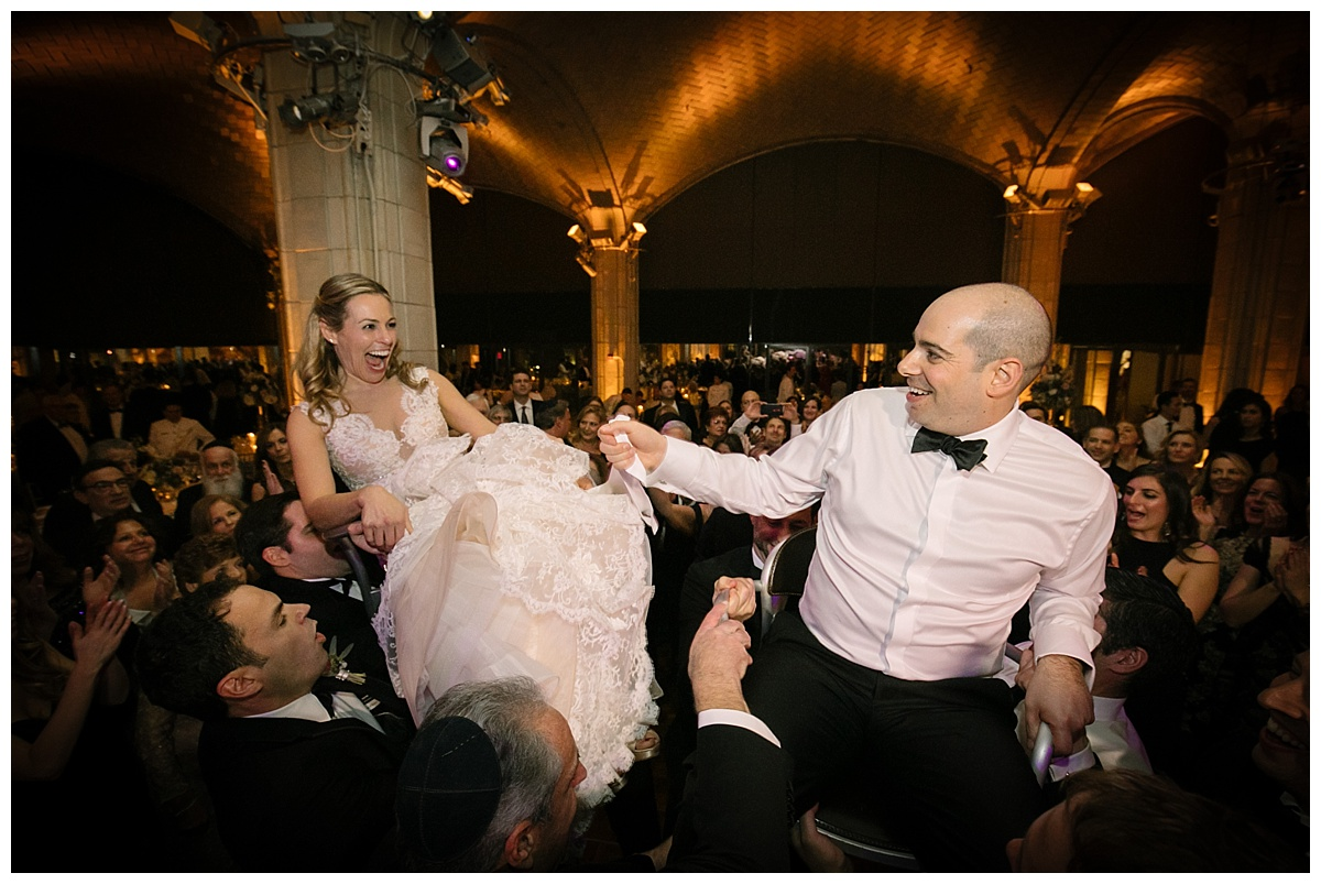 A chair dance or a horah during a wedding reception at Guastavinos in New York City. Dress by Ines Di Santo.