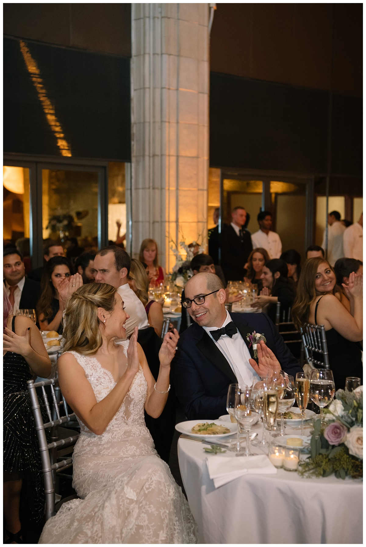 A newly wedded couple listening to a speech from their wedding guests during a wedding reception at Guastavinos in New York City. Dress by Ines Di Santo.