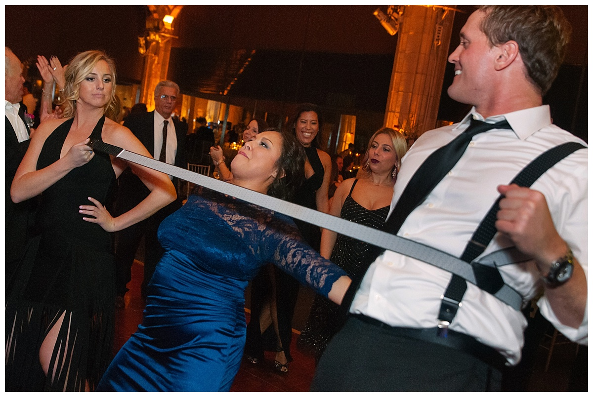 Wedding guests playing a limbo during a wedding reception at Guastavinos in New York City.
