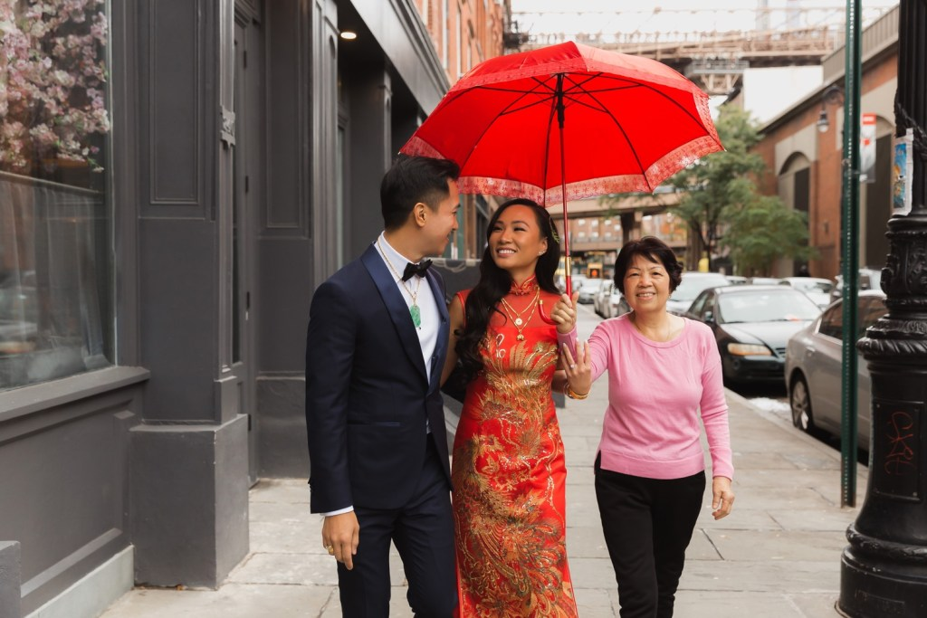 A portrait of a groom and a bride along with the bride's aunt walking near Mr. C Seaport Hotel on a wedding day at Cipriani Wall Street in New York City.