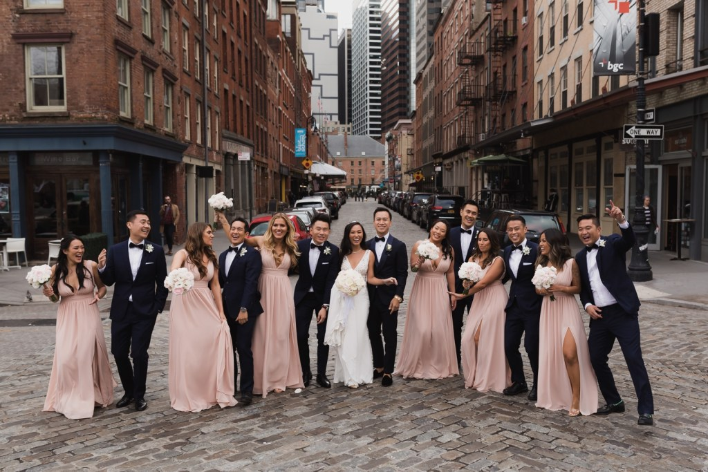 A portrait session of a couple and their wedding party near Mr. C Seaport Hotel on a wedding day at Cipriani Hotel in New York City.