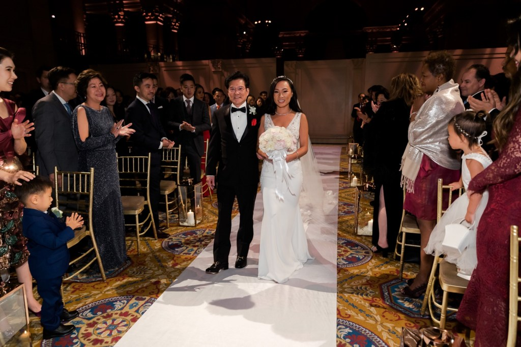 A bride and her father walking in an aisle during a wedding ceremony at Cipriani Wall Street in New York City.