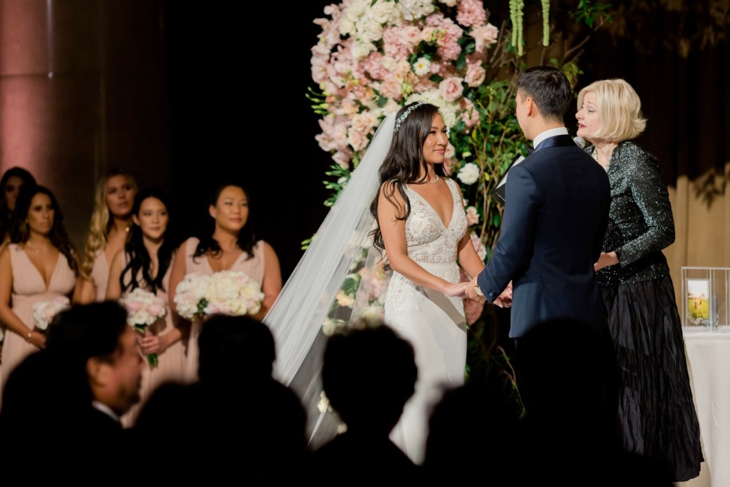 A groom and a bride during a wedding ceremony at Cipriani Wall Street in New York City. Wedding Dress by Pronovias