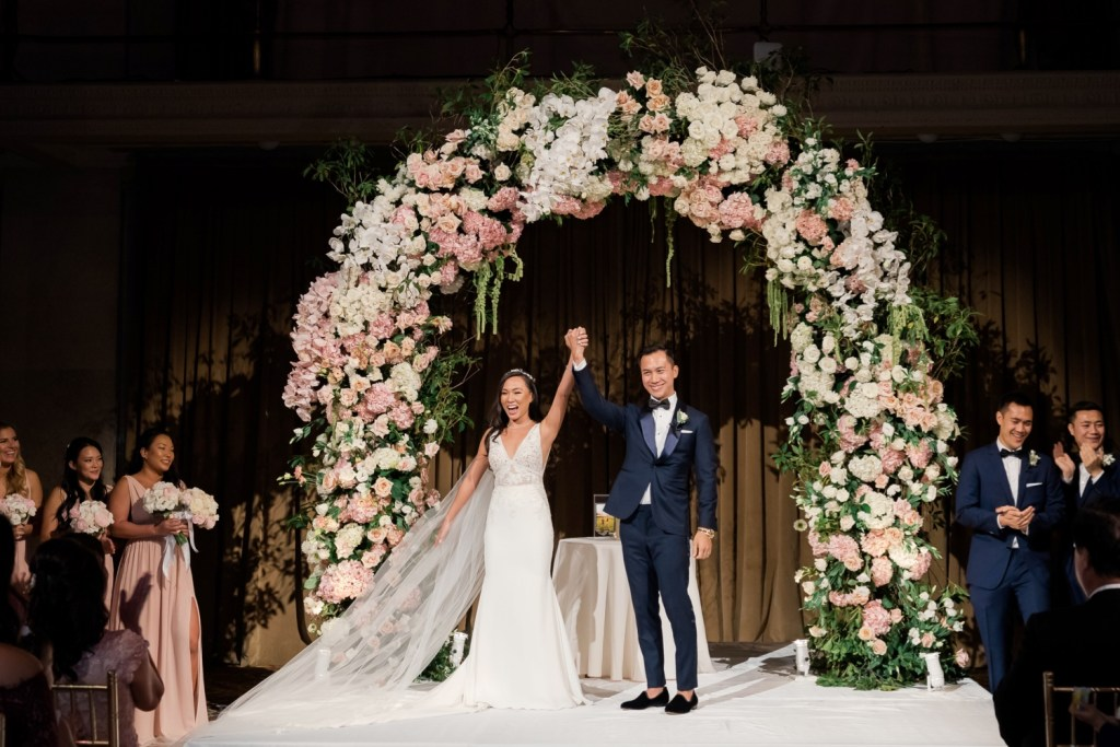 A newly wedded couple celebrating their marriage at Cipriani Wall Street in New York City. Wedding Dress by Pronovias