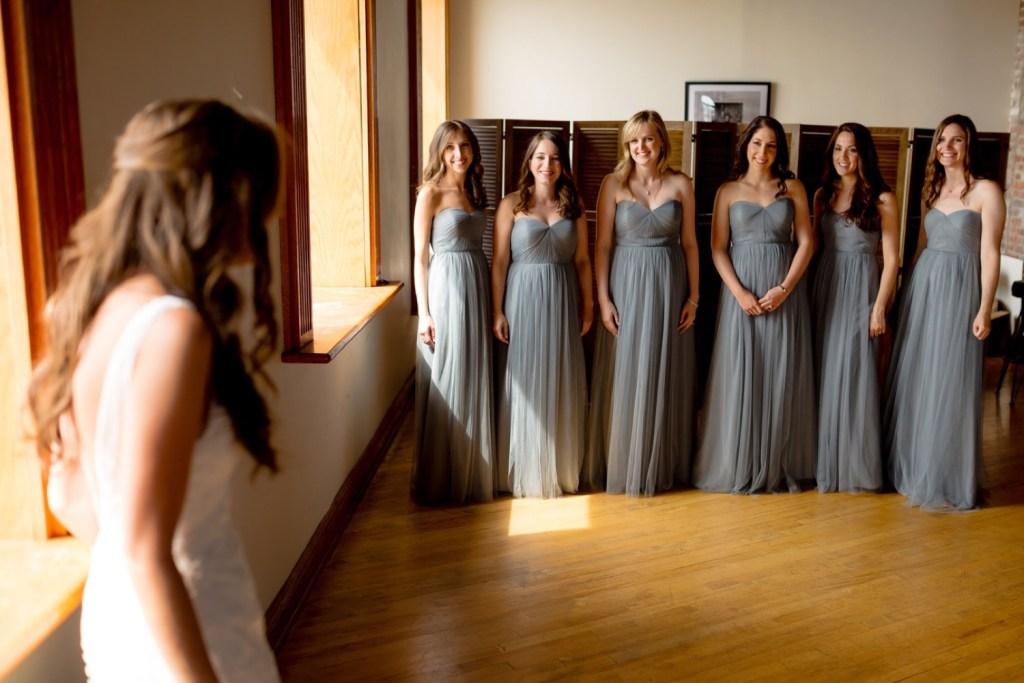 Bridesmaids looking at their bride inside a Liberty warehouse, Brooklyn New York.