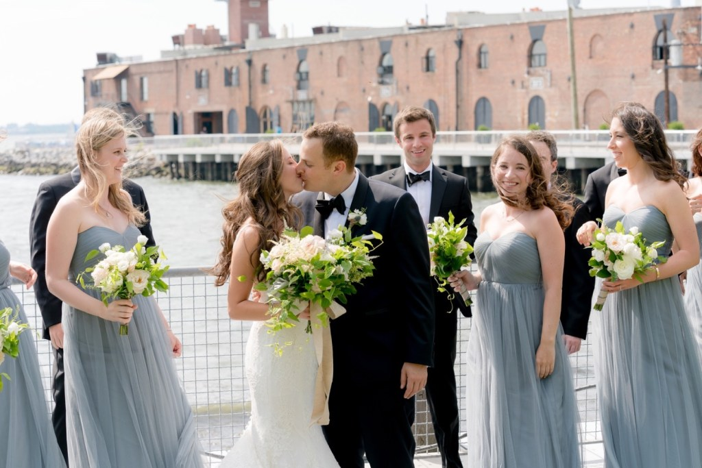 A portrait session of a bride and a groom, surrounded by their wedding parties, near Liberty Warehouse, Brooklyn New York.