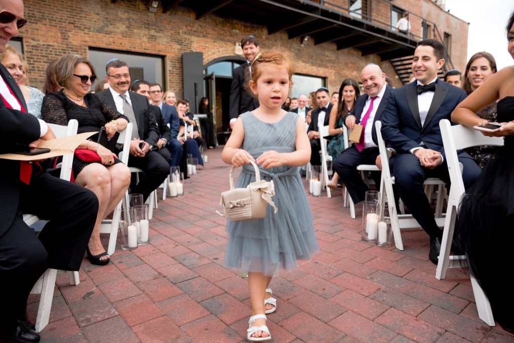 A flower girl walking in an aisle during a wedding ceremony at Liberty Warehouse, Brooklyn New York.